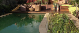 View over fresh water pool, landscaping and deck with outdoor furnitures