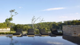 View from the surface of infinity pool with sun chairs and view over forrest and ocean.
