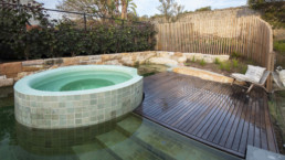 End of natural pool facing from the house with wet deck, jacuzzi and fencing.