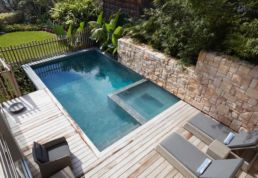 Aerial view of full Pool and spa with garden and decking around.