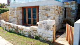 Hand-shaped stone cladding and backyard with wooden gate